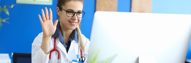 Smiling woman doctor welcomes the patient online