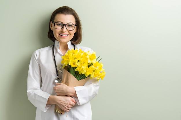 Smiling woman doctor with bouquet