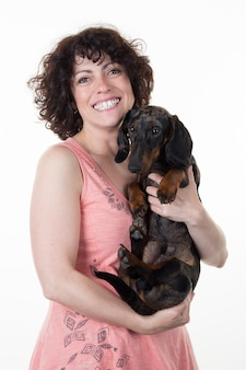 Smiling woman and a dog tender hugs isolated on white