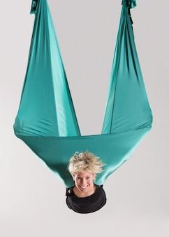 空中で空中ヨガを行う笑顔の女性