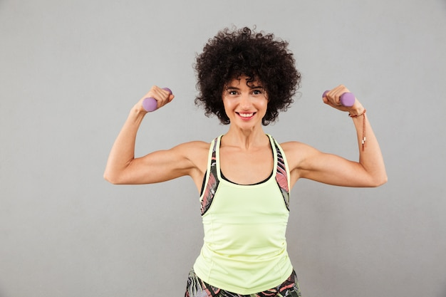 Smiling woman doing exercise with dumbbells and showing her biceps