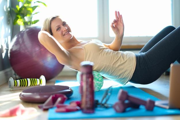 Улыбающаяся женщина делает упражнения на заднем ролике. рекомендуемые спортивные упражнения для концепции осанки