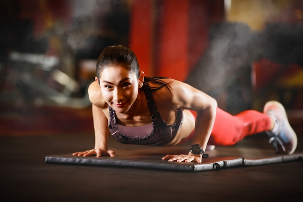 Smiling woman doing plank