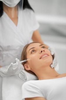 Улыбающаяся женщина делает процедуру для подтяжки кожи