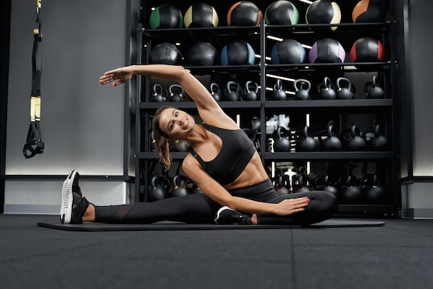 Smiling woman doing stretching in modern gym