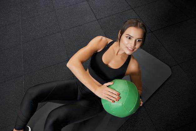 Улыбающаяся женщина делает тренировку с зеленым мячом