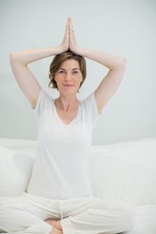 Улыбающаяся женщина делает упражнения йоги на кровати в спальне дома