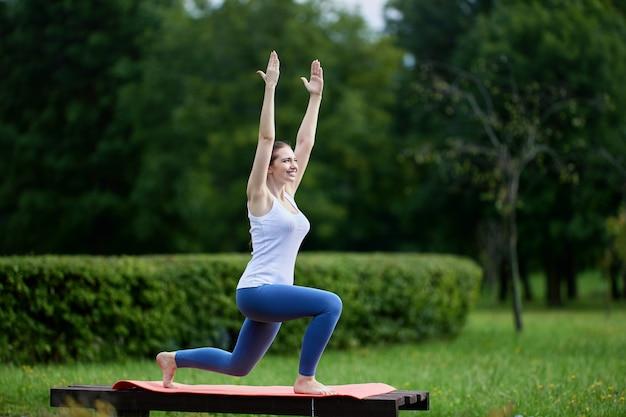 膝の上に立って手を上げてヨガの練習をしている笑顔の女性