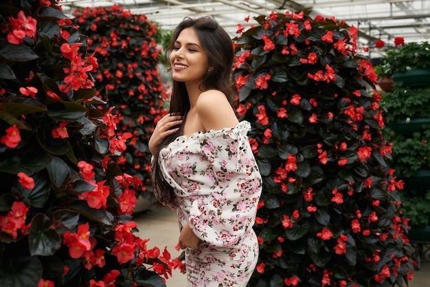 Smiling woman in dress posing near beautiful red flowers