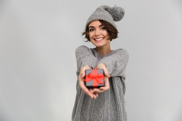 Smiling woman dressed in sweater give you a gift.