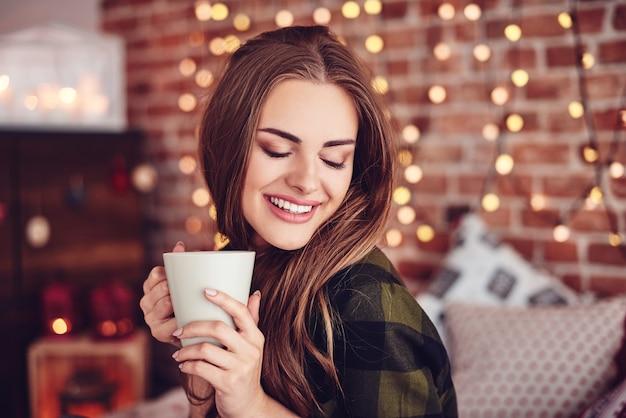 家でコーヒーを飲む笑顔の女性
