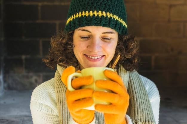 Smiling woman drinking hot beverage