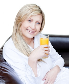 Smiling woman drinking an orange jus