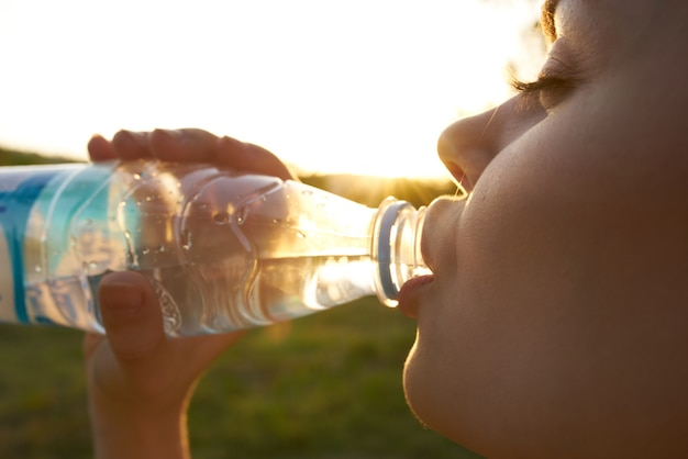 Smiling woman drinking water close up nature