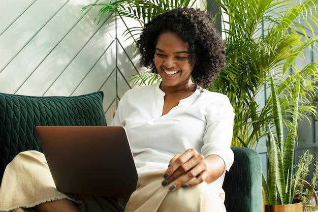 새로운 표준에서 집에서 일하는 노트북으로 전화 회의를 하는 동안 웃고 있는 여성