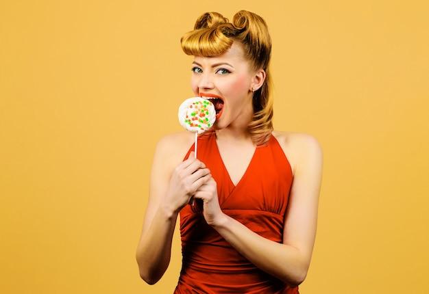 笑顔の女性はロリポップ、キャンディー、甘い菓子とファッションの髪型を持つセクシーなブロンドの女の子を食べます。