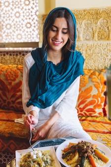 Donna sorridente che mangia nel ristorante arabo
