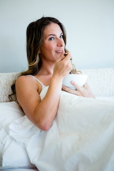 Smiling woman eating a bowl of cereal lying in her bed