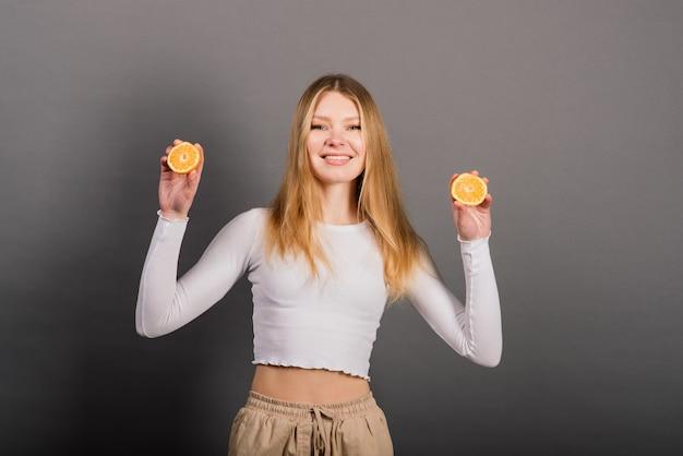 Улыбающаяся женщина ест апельсин, половину фруктов, длинные волосы. студийный снимок