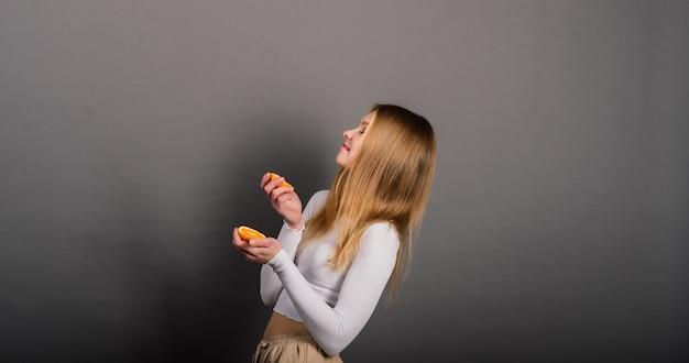 Улыбающаяся женщина ест апельсин в студии, половина фруктов, светлые длинные волосы.