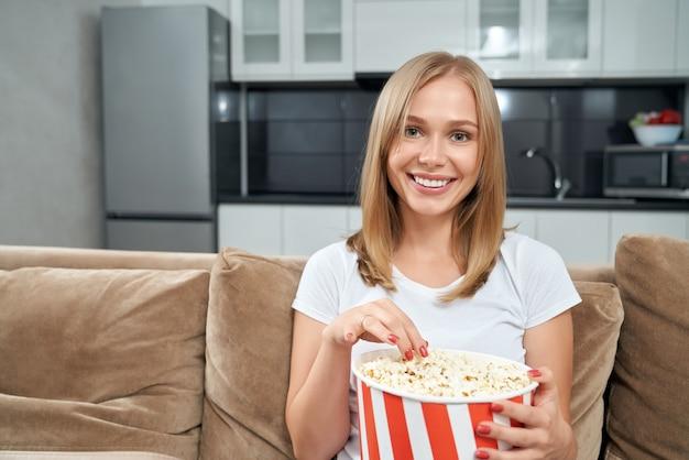 Улыбающаяся женщина ест попкорн, сидя на диване