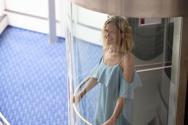 웃는 여자는 호텔과 쇼핑 센터 개념의 투명한 엘리베이터 엘리베이터에서 먹는다