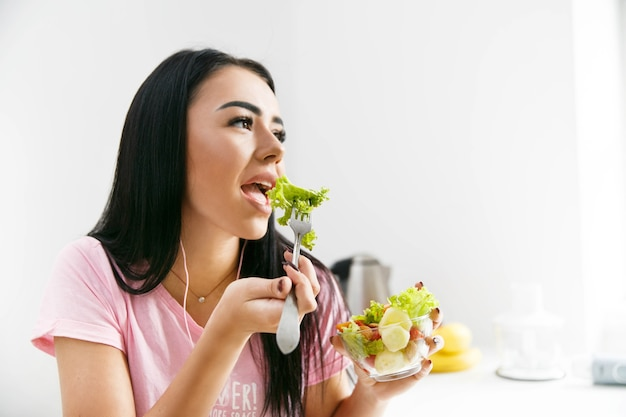 Smiling woman eats salad in the white kitchen