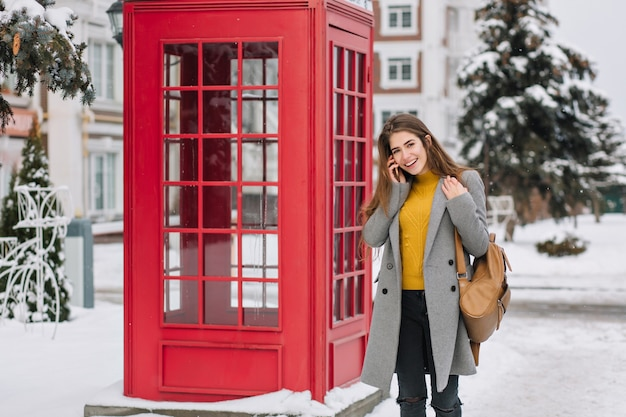 Smiling woman in elegant attire talking on smartphone while standing near british phone booth in winter. outdoor photo of pleased brunette woman in trendy coat carrying brown backpack during walk.