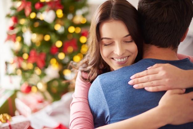 クリスマスに彼女のボーイフレンドを抱きしめる笑顔の女性