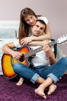 Smiling woman embracing her boyfriend playing guitar