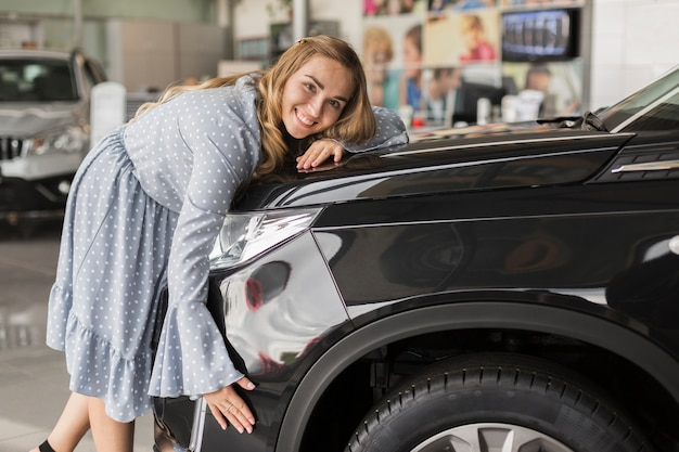 Smiling woman embracing modern car