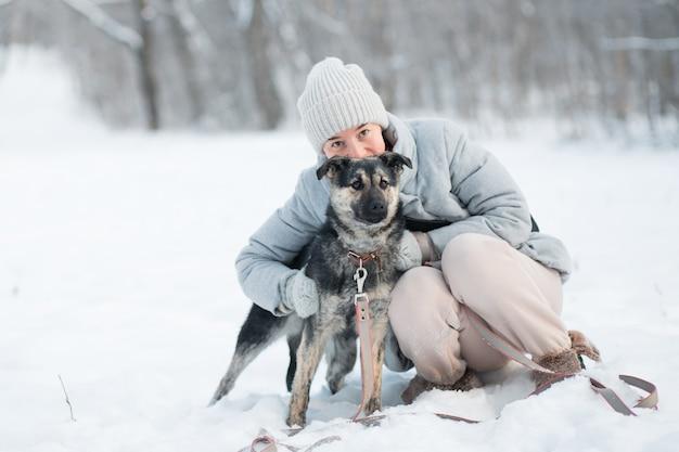 冬の森で雑種犬を抱きしめる笑顔の女性。