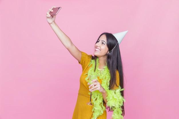 ピンクの背景に自己肖像画を取ってパーティーで楽しんで笑顔の女性