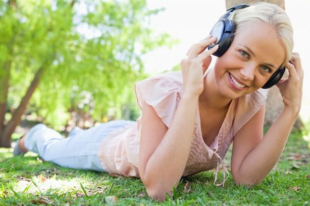 Smiling woman enjoying music on the grass
