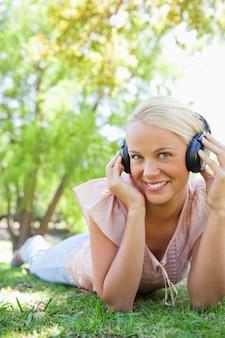 Smiling woman enjoying music on the lawn