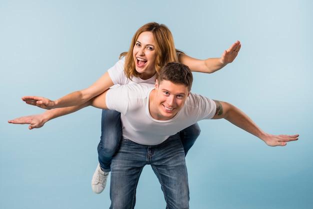 Smiling woman enjoying the piggyback ride on her boyfriend's back against blue backdrop