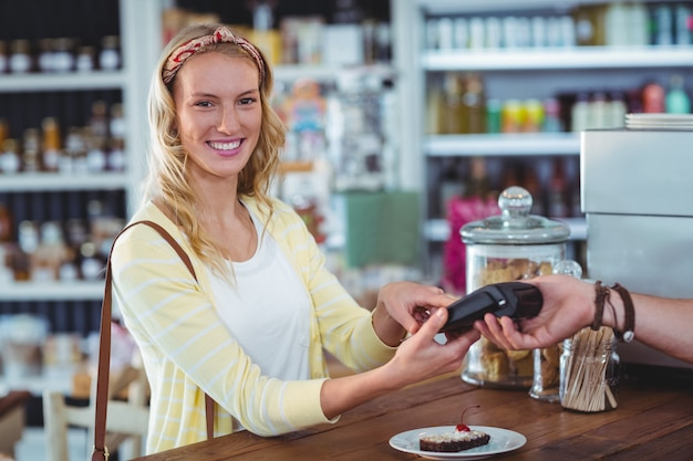 Smiling woman entering pin number into machine at counter