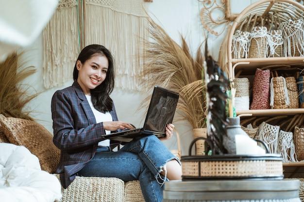 Улыбающаяся женщина-предприниматель смотрит, используя ноутбук, сидя в ремесленной мастерской