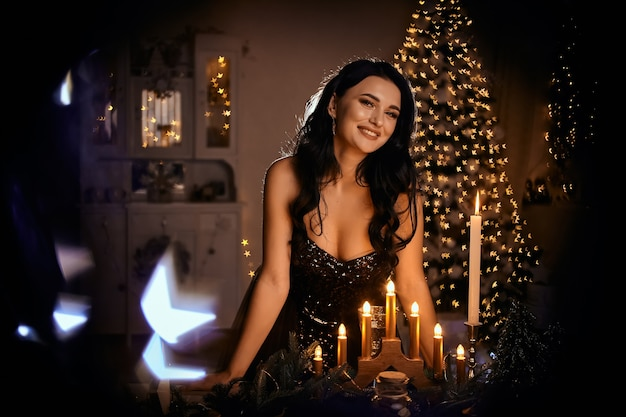 Smiling woman in evening dress with glass of sparkling wine over night lights
