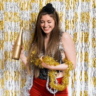 Smiling woman in evening wear with bottle of drink and tinsel