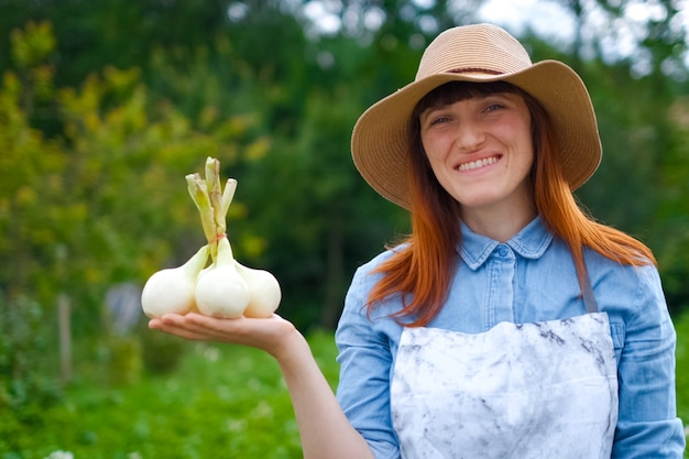 Smiling woman farmer gardener holding fresh dug garlic plant in hand