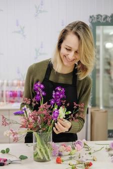 笑顔の女性花屋は花を切り花瓶に入れます