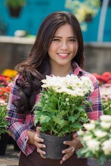 Smiling woman florist holding flowerpot
