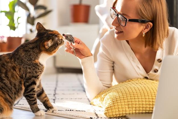 笑顔の女性フリーランサーがリビングルームのカーペットの上にあり、自宅で猫とおもちゃのマウスで遊ぶ
