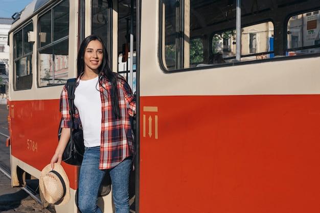 路面電車から降りて、よそ見笑顔の女性