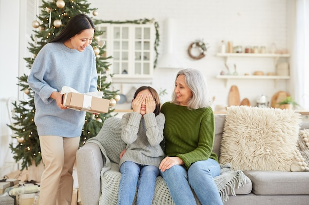 Smiling woman giving christmas present to her little sister while they sitting on sofa and celebrating christmas