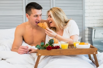 Smiling woman giving croissant to man in bed near food on breakfast table