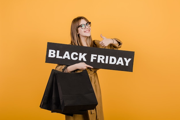 Smiling woman in glasses with black friday sign and paper shopping bags isolated over yellow