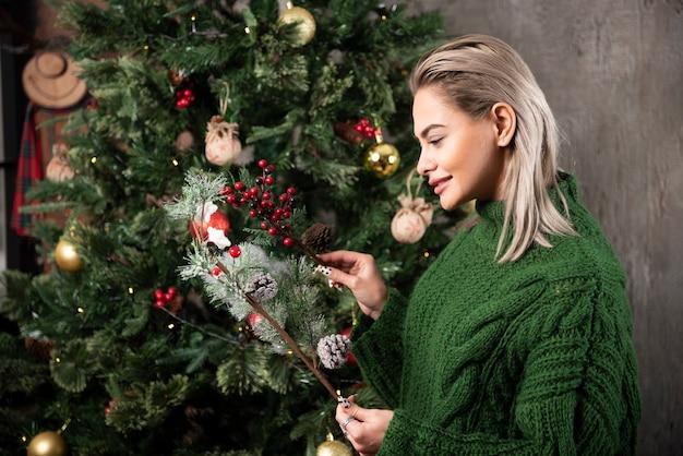 Donna sorridente in maglione caldo verde in piedi e in posa vicino a un albero di natale