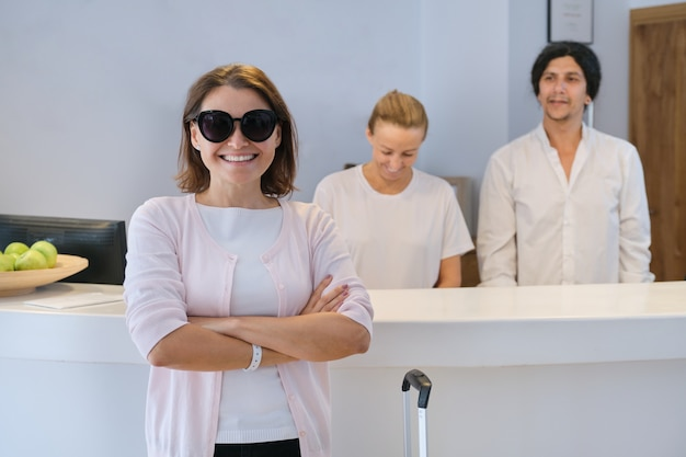 Smiling woman guest near reception desk, friendly man and woman hotel workers